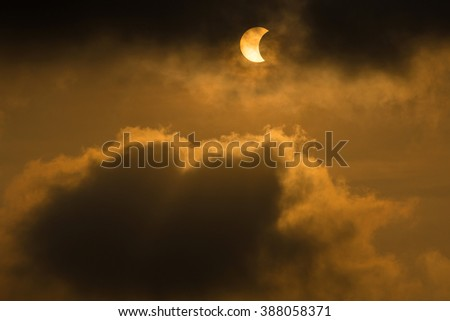 The Moon covering the Sun in a partial eclipse with dramatic cloud. Scientific background, astronomical phenomenon. - stock photo