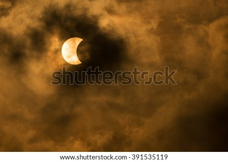 The Moon covering the Sun in a partial eclipse with dramatic cloud. Scientific background, astronomical phenomenon - stock photo