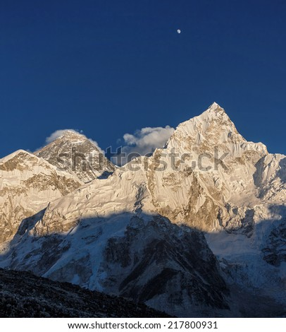 The Moon, Mt. Everest (8848 m), and Nuptse (7864 m) in the evening. View from Kala Patthar (5600 m) - Nepal, Himalayas - stock photo