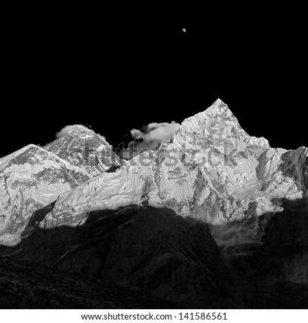 The Moon, Mt. Everest (8848 m), and Nuptse (7864 m) in the evening (view from Kala Patthar) - Nepal, Himalayas (black and white) - stock photo
