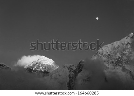 The Moon, Mt. Everest (8848 m), and slope of the Nuptse (7864 m) at sunset (view from Kala Patthar) - Nepal, Himalayas (black and white) - stock photo