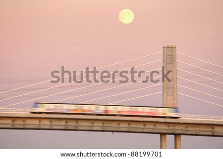 The moon rises behind the new Canada Line, a rapid transit commuter train, that crosses the Fraser River from Vancouver into Richmond and the airport. British Columbia, Canada. - stock photo