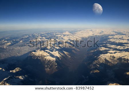 The Moon rises over planet Earth. Italian Dolomites in the foreground. - stock photo