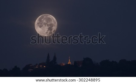 the moon setting  behind a temple
