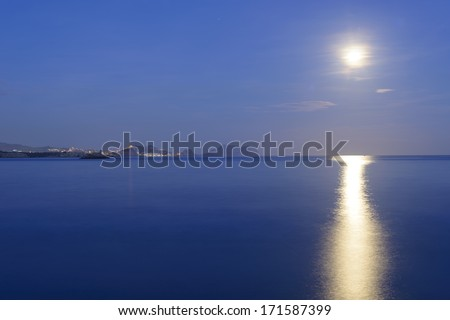 The moon shines in the ocean at night  reflecting in the water in Aguilas, Murcia, Spain - stock photo