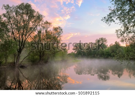 The morning landscape with fog and warm sky over the Narew river, Poland. - stock photo