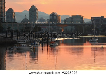 The morning light on the condominiums and anchored boats of Vancouver's Yaletown neighbourhood reflect in False Creek. British Columbia, Canada.