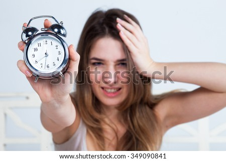 The morning of young beautiful girl in bed with the clock service at home - stock photo