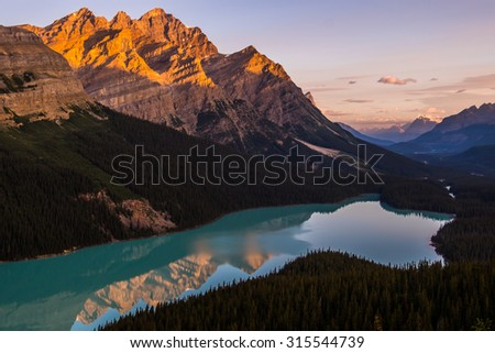 The morning sun lights up Peyto Peak over Peyto Lake, Banff National Park, Canada., - stock photo