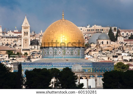 The morning sun shines on the golden Dome of the Rock and church steeples on the skyline of the Old City of Jerusalem. - stock photo
