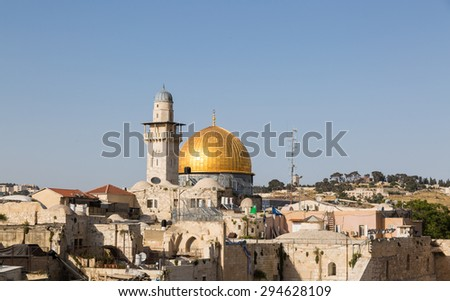 The mosque of Al-aqsa (Dome of the Rock), minaret and roofs  in Jerusalem with doves in sky - stock photo