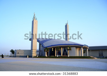 The mosque outside the Khalifa sports stadium at Aspire Academy in Doha, Qatar, with an unidentifiable Muslim woman passing by. - stock photo