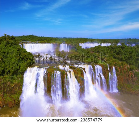 The most famous waterfalls in the world - Iguazu. Magnificent rainbow is above the thundering water jets. The Brazilian side of the falls - stock photo