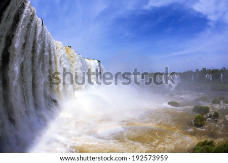 The most high-water waterfall in the world - Iguazu. White whipped foam of water and a thin mist over the water. The picture is taken by lens Fisheye - stock photo