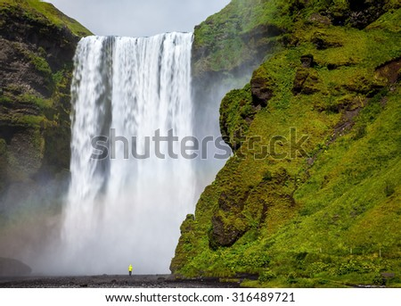 The most popular waterfall in Iceland - Skogafoss. Water rushes down with a crash, forming a cloud of mist. Picturesque huge rainbow appears in the water mist - stock photo