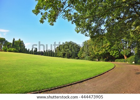 The most romantic landscape park garden in Italy. Comfortable walking path goes through the green grassy lawn - stock photo