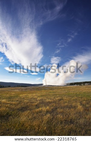 The most well-known of the world geyser in Yellowstone national park - Old Faithful. The beginning of eruption - stock photo