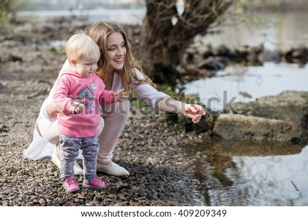 The mother and her child on the bank of the river