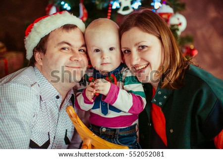 The mother,father and son sitting near Christmas tree