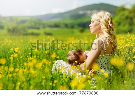 The mother feeds the young child feeding in the countryside. Breast-feeding - stock photo
