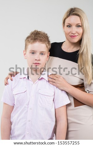 The mother in a beige dress hugging son in a pink shirt in the studio - stock photo