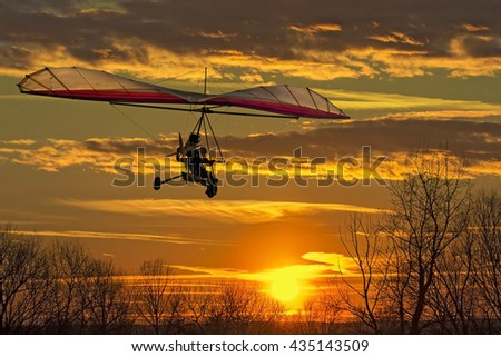 The motorized hang glider fly in the sunset  - stock photo