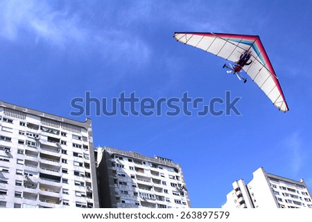 The motorized hang glider flying over residential buildings in the city - stock photo