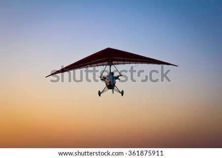 The motorized hang glider in the sky - stock photo