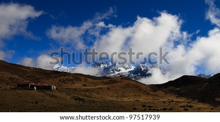 The mountain plateau and the high snow-capped mountains with clouds