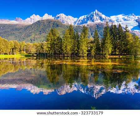The mountain resort of Chamonix.  City Park is illuminated by the setting sun. The lake reflected the snow-capped Alps and evergreen spruce - stock photo