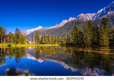 The mountain resort of Chamonix, Haute-Savoie. City Park is illuminated by the setting sun. The lake reflected the snow-capped Alps and evergreen spruce