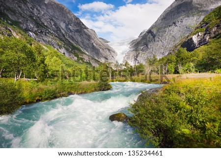 The mountain river, against the woody mountains, originating from a thawing glacier, Norway - stock photo