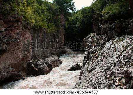 The mountain river in the gorge. tourist walks. - stock photo