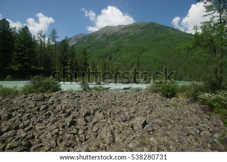 The mountain river in the mountains. Current through the gorge the river. Stones and rocky land near the river. Beautiful mountain landscape.