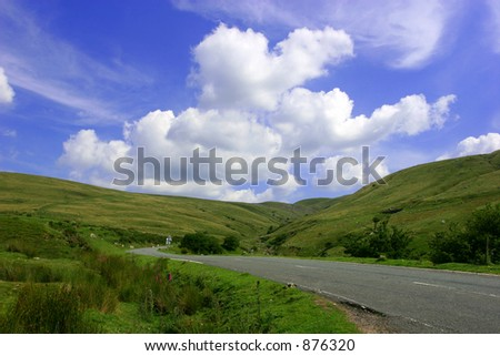 The Mountain Road, with hills on either side in the  Brecon Beacons National Park, Wales, United Kingdom set against a backdrop of blue sky and clouds.