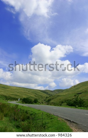 The Mountain Road, with hills on either side,  in the  Brecon Beacons National Park, Wales, United Kingdom set against a backdrop of blue sky and puffy white clouds. - stock photo