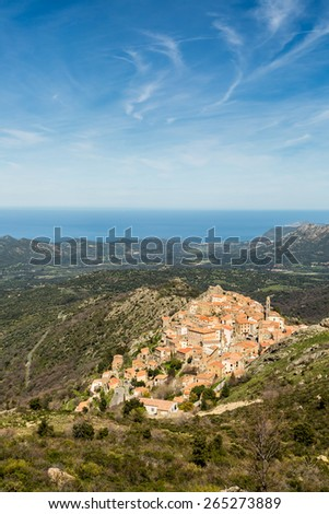 The mountain village of Speloncato in the Balagne region of north Corsica with maquis and the Mediterranean in the background against a blue sky and wispy clouds