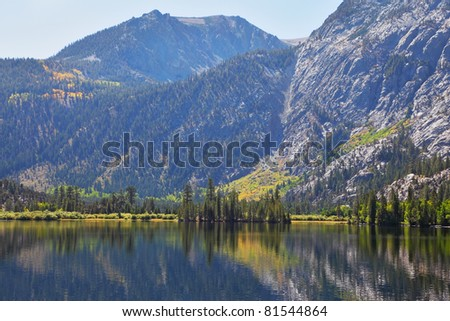 The mountains are reflected in the smooth water of a picturesque lake