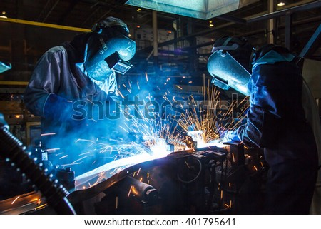 The movement of workers with protective mask welding metal. - stock photo