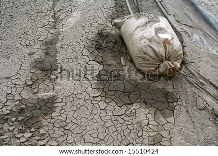The mud from a flood continued to dry out with a sandbag as a reminder of the devastating floods. - stock photo