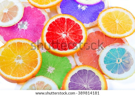 The multi-colored citrus of artificial color cut by circles lies on a table. Orange, lemon, grapefruit. Colors not usual for a citrus. Close up, small depth of sharpness - stock photo