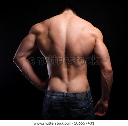 The muscular male back on black background. - stock photo