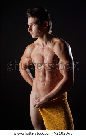 The muscular young nude wet sexy boy wrapped in yellow towel - stock photo