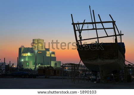 The Museum of Islamic Art, Doha, Qatar, seen from the dhow repair shipyard, with a dhow under maintenance silhouetted against the sunrise. - stock photo