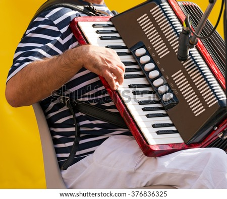 The Musician Playing the Accordion / Detail of a Spanish accordionist while he is playing the accordion during a concert - stock photo