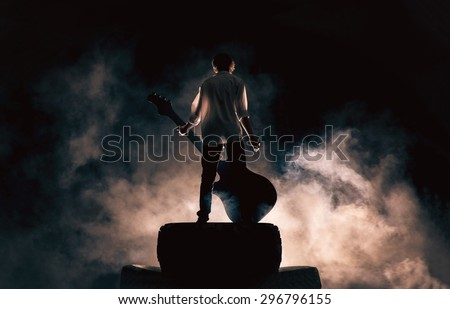 The musician plays on a large rock guitar in a great smoke, rock music, concert and festival - stock photo