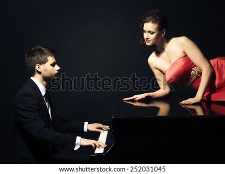 The musician plays the old piano nearby the seductive woman - stock photo