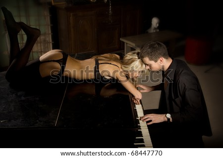 The musician plays the old piano nearby the seductive woman