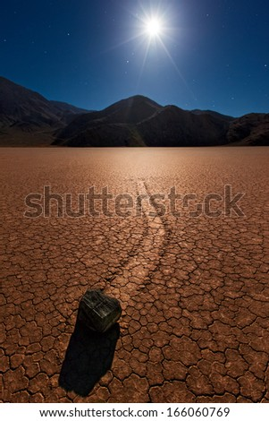 The mysterious moving rocks of the Race Track in Death Valley National Park under a full moon.  - stock photo
