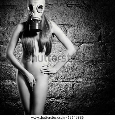 The naked beautiful young girl in a gas mask - stock photo